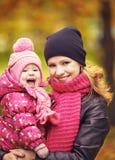 步行的妈妈和小女儿在秋天 免版税库存照片
