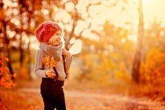 步行的愉快的儿童女孩在秋天森林里 免版税库存图片