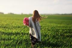 步行的美丽的年轻女人,花的女孩 E 有牡丹步行的一个女孩在领域 免版税库存图片