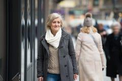 步行的美丽的资深妇女在城市 冬天 免版税库存照片