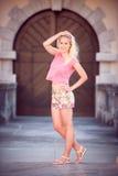 步行的美丽的年轻白肤金发的妇女在城市附近 库存照片