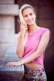 步行的美丽的年轻白肤金发的妇女在城市附近 免版税图库摄影