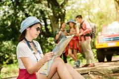步行的远足者查找映射 驾驶一起微笑的夫妇或朋友愉快在野营的旅行暴涨期间户外在森林里 免版税库存照片