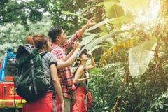 步行的远足者查找映射 驾驶一起微笑的夫妇或朋友愉快在野营的旅行暴涨期间户外在森林里 免版税图库摄影