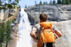 步行的远足者看瀑布在优胜美地公园 免版税库存图片