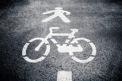 步行者和周期在沥青的车道标志 免版税库存图片