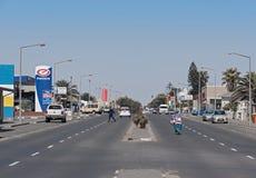 步行者和汽车在山姆Nujome Ave在斯瓦科普蒙德,纳米比亚 库存图片
