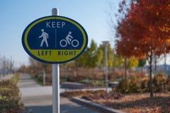 步行者和骑自行车者的一个标志在公园 免版税库存照片