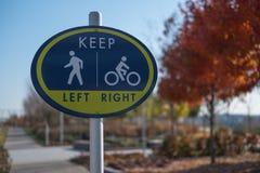 步行者和骑自行车者的一个标志在公园 免版税库存图片