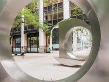 步行者在东西方门雕塑,更低的Manhatt反射了 免版税库存图片