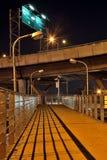 步行者的桥梁在高速公路下在晚上 库存图片