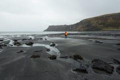 步行通过沿坚固性海岸线的苏格兰高地的人 免版税库存照片