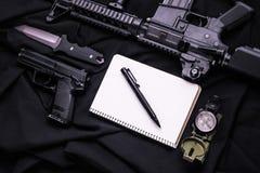武器、笔记本、笔、刀子和指南针在黑织品 免版税图库摄影