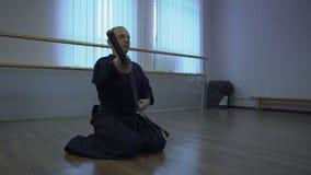 武士坐地板并且做弓,采取说谎在他自己前和打扮他的katana ` s剑在 股票录像