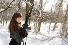 武装的妇女在冬天森林里 库存图片