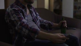 歪斜男性在手中打手势与遥控在电视机,啤酒前面,恼怒 股票录像