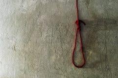 死亡的红色绳索非陷阱在水泥墙壁上 图库摄影