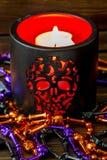 死的蜡烛的万圣夜背景和各种各样伏都教在一张黑暗的木桌上成串珠状 免版税库存图片