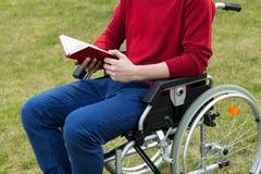 残疾人阅读书在庭院里 免版税库存照片