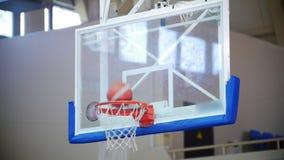 残疾在篮球篮的球员投掷的球后面看法,球击中圆环和比分 股票录像