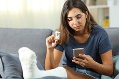 残疾妇女咨询的药片信息在网上 免版税库存照片
