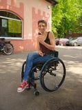 残疾妇女微笑和被吃的冰淇凌,都市场面 免版税库存照片