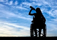 残疾妇女的剪影轮椅饮用水的从塑料瓶 图库摄影