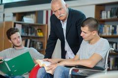 残疾学生在有朋友和图书管理员的学校图书馆里 免版税图库摄影