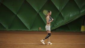 残疾少妇通过有球拍的网球场走 在姿态的立场 为比赛准备 股票录像