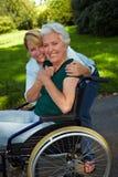 残疾拥抱的护士前辈 免版税库存图片