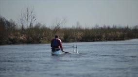 残疾运动员划船背面图在河的独木舟的 荡桨,乘独木舟,用浆划 ?? 划皮船 股票视频