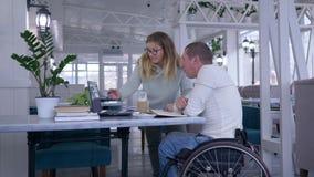 残疾,愉快的不适的学生资深男性的教学在有在家期间学习使用膝上型计算机的教育家妇女的轮椅 股票视频