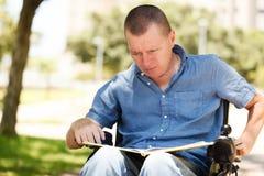 残疾读书在公园的一本书 库存图片