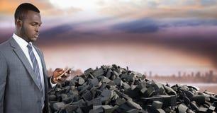 残破的具体石堆和商人在电话在都市风景 免版税库存图片