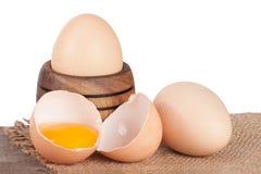残破的在一张木桌上的鸡蛋用卵黄质和蛋壳有白色背景 免版税库存图片