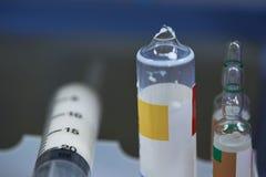 残破的小瓶在手术室和塑料注射器的麻醉的药物使用后 库存图片