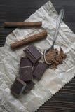 残破的巧克力块和香料在木桌上 库存图片