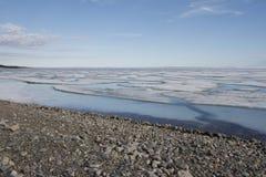 残破的平底锅在海洋的海冰沿岸航行与蓝天和Pebble海滩沿西北段落 免版税库存图片