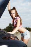 残破的汽车她性感的妇女 免版税图库摄影