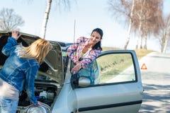 残破的汽车有问题开始二名妇女 图库摄影