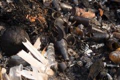 残破的玻璃瓶和垃圾在被烧的垃圾 免版税图库摄影