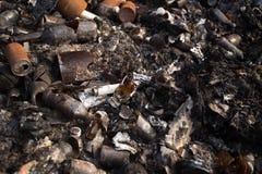 残破的玻璃瓶和垃圾在被烧的垃圾 免版税库存照片