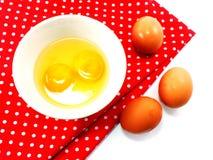 残破的蛋壳用在陶瓷碗的蛋黄有红色圆点织品的 免版税库存照片