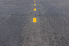 残破的车道的黄色小点线在柏油路,路标 库存图片
