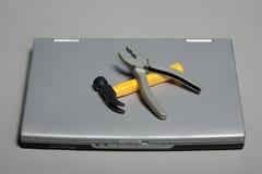 残破的锤子膝上型计算机钳子 免版税库存照片