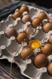 残破的鸡蛋卵黄质在蛋壳的和在纸盒的几个鸡蛋怂恿bo 免版税库存图片