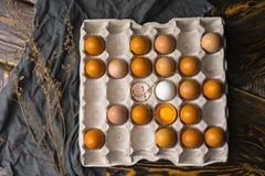 残破的鸡蛋卵黄质在蛋壳的和在纸盒的几个鸡蛋怂恿bo 库存图片