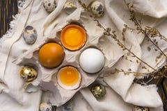 残破的鸡蛋卵黄质在蛋壳的在纸盒蛋盒和鹌鹑蛋 免版税图库摄影
