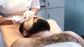残酷深色头发的人在医疗中心的得到医疗痣和刺瘤去除做法 医生去除刺瘤  股票录像