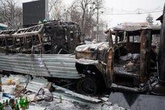 残破和完全地被烧的汽车和公共汽车在占领雪城市巨型的护拦在反政府抗议期间 库存图片